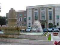 Nell'immagine sullo sfondo il Palazzo del Governo, in primo piano la fontana di Piazza della Libertà